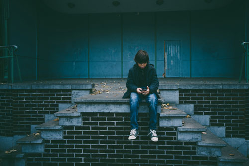 Young boy sitting on abandoned steps looking at cell phone