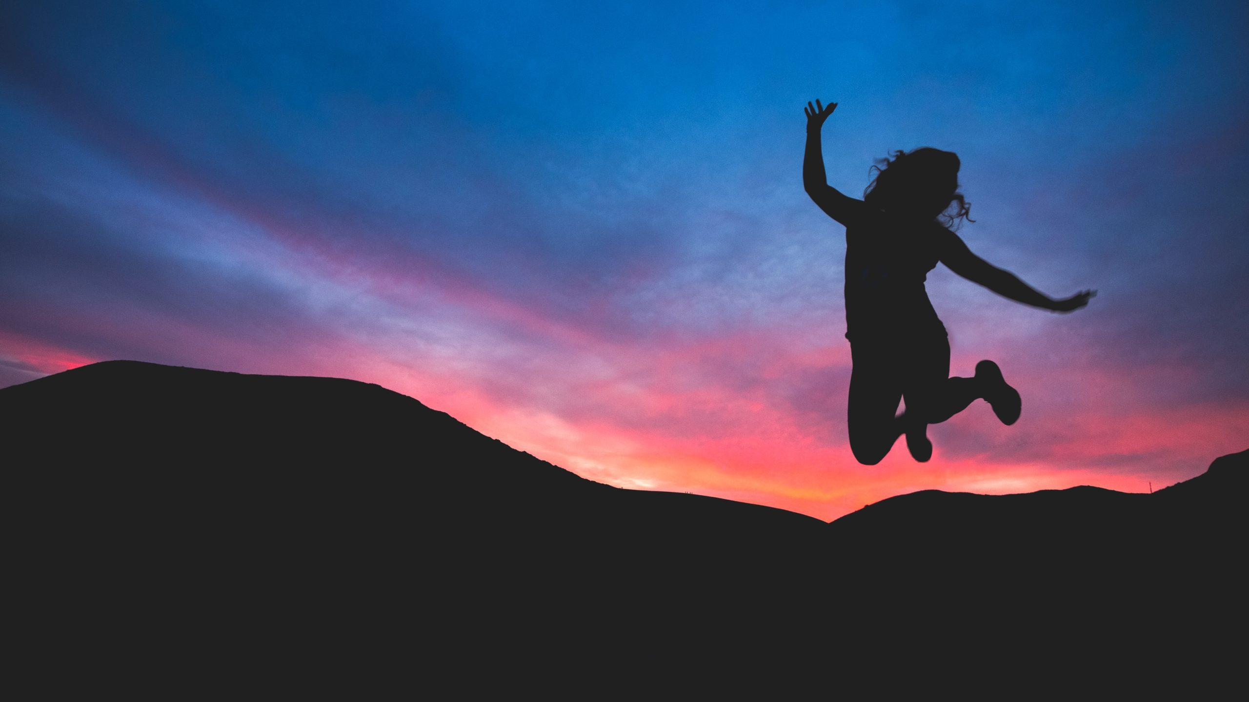 Person jumping in front of a sunset